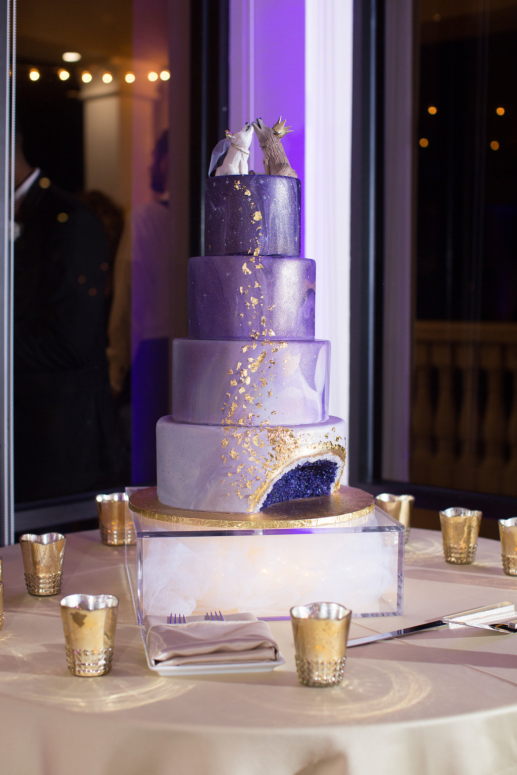 Four Tier Marble Ombre Enchanted Magical Purple and Champagne Cake and Amethyst Geode, Gold Leafing Painted Cascading Stars and Shimmer Airbrushing with Custom Wolf and Fox Cake Topper on Acrylic Cake Stand and Gold Votive Candle Holders on Champagne Tablecloth   Clearwater Beach Wedding Venue Feather Sound Country Club   St. Petersburg Wedding Baker The Artistic Whisk