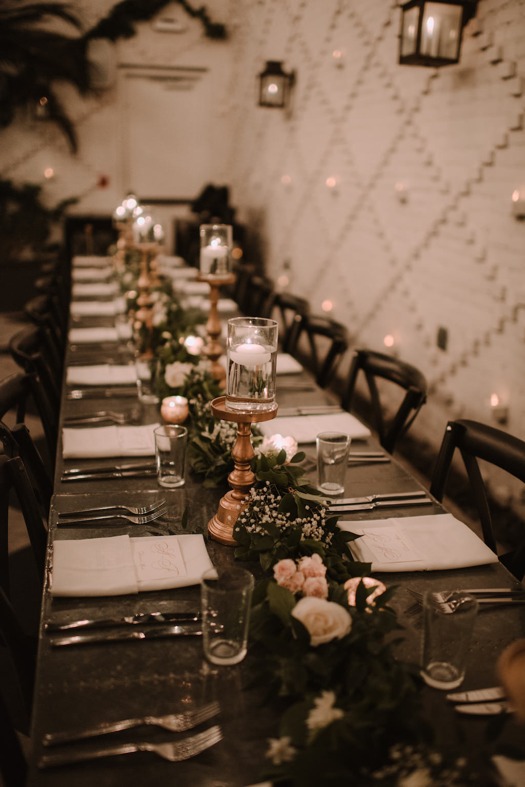 Romantic Intimate Atrium Wedding Reception Decor with Long Metal Feasting Tables with Greenery Garland and White Roses and Baby's Breath Centerpiece, Black Crossback Chairs, White Linen Napkins, Gold Candlesticks and Floating Candles | South Tampa Historic Wedding Venue The Oxford Exchange