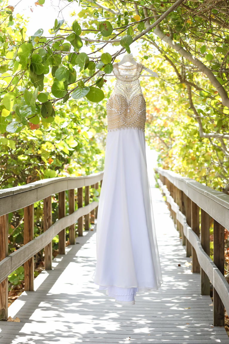 A-Line Scoop Neck Nude Rhinestone Bodice and White Chiffon Floor Length Wedding Dress on Hanger Outdoors | Tampa Bay Wedding Photographer Lifelong Photography Studios
