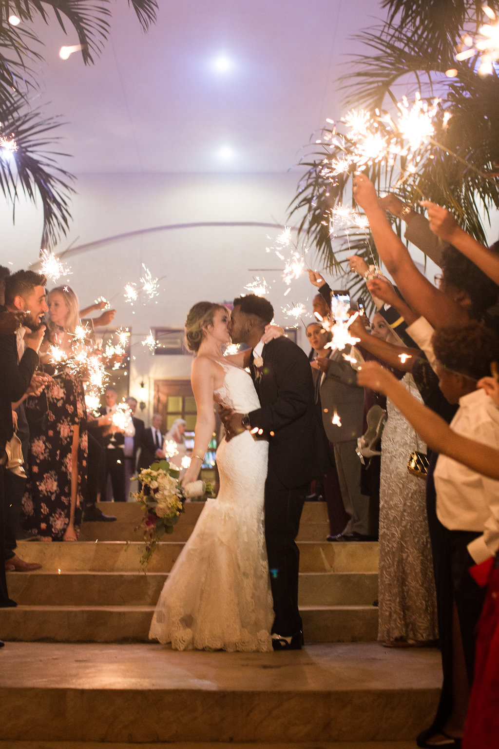 Outdoor Bride and Groom Sparkler Exit Portrait with Wedding Guests, Bride Wearing Spaghetti Strap Lace V-Neck Mermaid Wedding Dress, Updo, White, Deep Purple and Greenery Flower Bouquet, Groom Wearing Black Tuxedo   Clearwater Beach Wedding Venue Feather Sound Country Club
