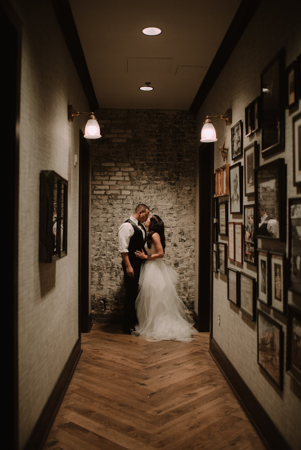 Indoor Wedding Portrait in Hallway with Whitewash Brick Backdrop, Bride in Sweetheart Strapless Tulle Wedding Dress with Rhinestone Belt, Groom in Black Vest with Black Bowtie | South Tampa Historic Wedding Venue The Oxford Exchange | Bridal Shop The Bride Tampa