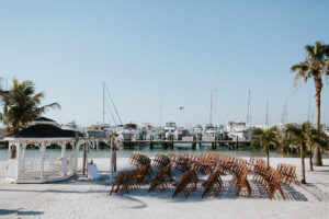 Outdoor Waterfront Beach Wedding Ceremony with Wedding Arch with White Draping and Wooden Ceremony Chairs | Tampa Bay Wedding Venue Isla Del Sol Yacht and Country Club