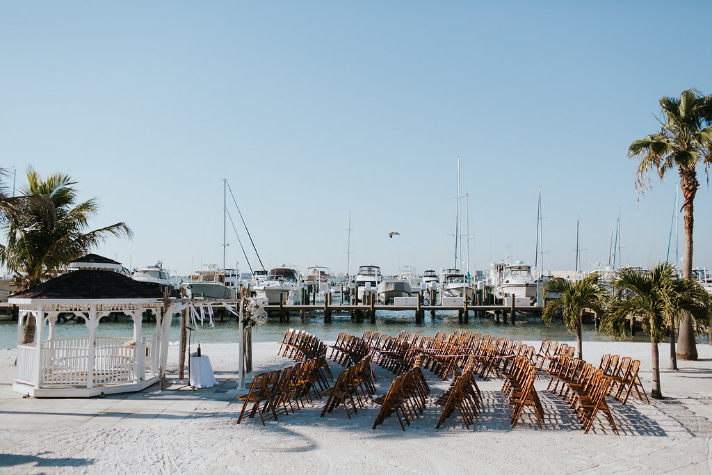 Outdoor Waterfront Beach Wedding Ceremony with Wedding Arch with White Draping and Wooden Ceremony Chairs   Tampa Bay Wedding Venue Isla Del Sol Yacht and Country Club