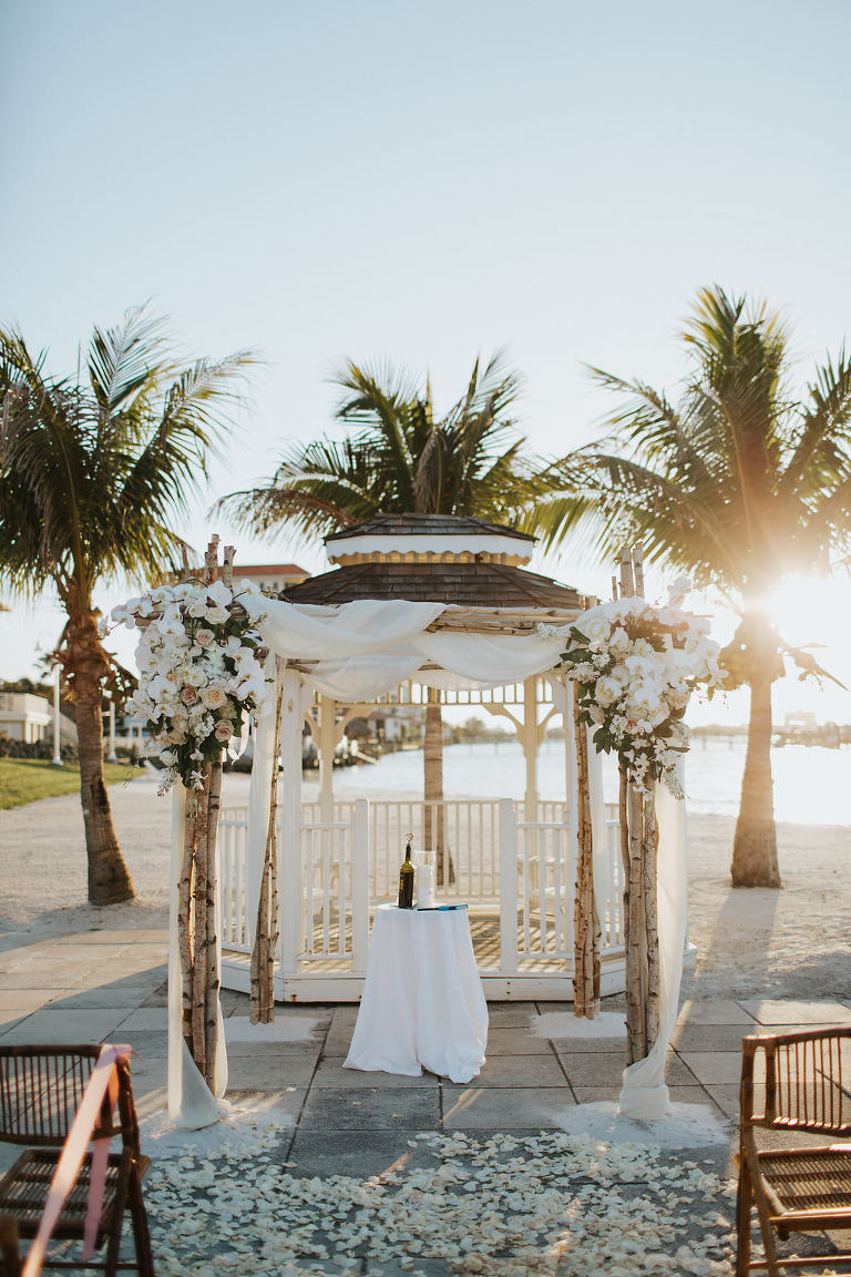 Outdoor Beach Wedding Ceremony at Gazebo with Birchwood Arch, White Draping and White Florals | Waterfront Venue Isla Del Sol Yacht and Country Club