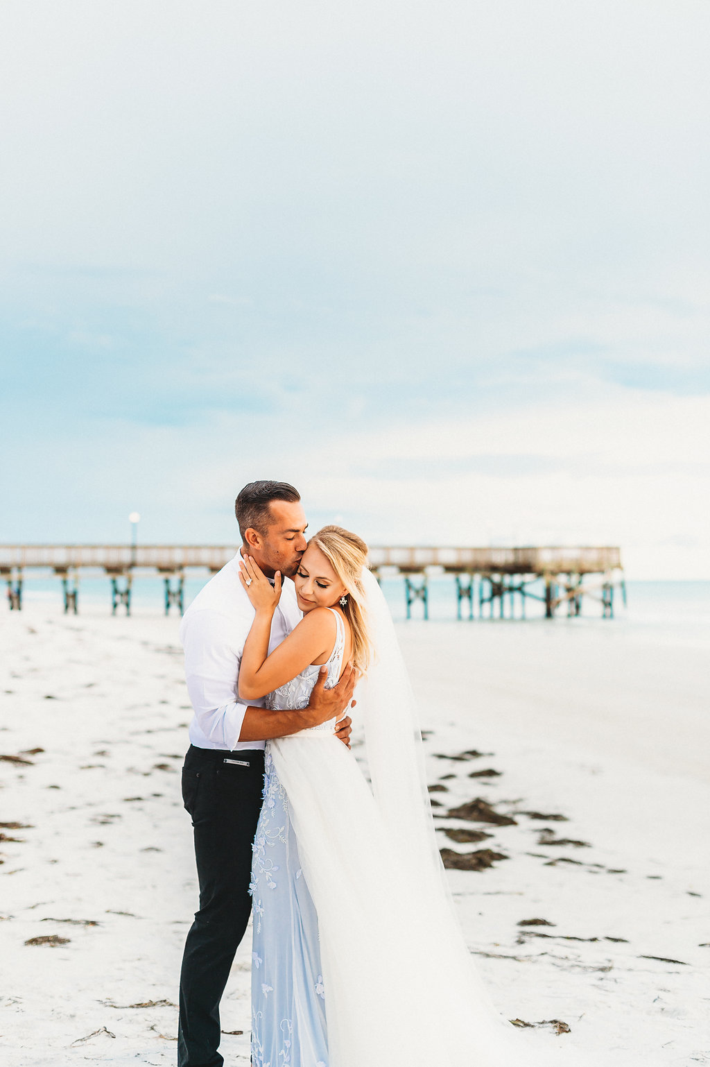 Coastal, St. Pete Beach Waterfront Bride and Groom Wedding Portrait, Bride in Sleeveless Illusion Neckline Floral Overlay and Light Blue Wedding Dress with Tulle Skirt and Veil