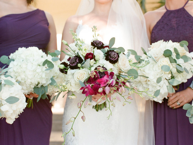 Bride and Bridesmaids Portrait, Bride with Organic White Roses, Pink and Deep Purple Flowers with Silver Dollar Eucalyptus Wearing Lace V-Neck Mermaid Wedding Dress, Bridesmaids Wearing Deep Purple Dresses and White Hydrangeas and Silver Dollar Eucalyptus Bouquets