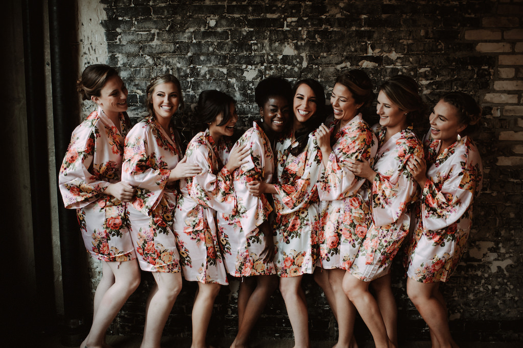 Indoor Bridal Party Getting Ready Portrait, Bridesmaids in Matching Pink and Floral Silk Robes, Bride in White Floral Silk Robe | Tampa Bay Wedding Venue Oxford Exchange