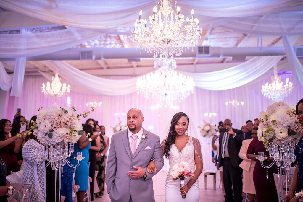 Bride Walking Down the Aisle Ceremony Portrait with Dad in V-neck Beaded Rhinestone Bodice Wedding Dress and Veil, Blush Pink Rose Bouquet, White Draping and Crystal Chandeliers   Tampa Bay Wedding Venue The Crystal Ballroom