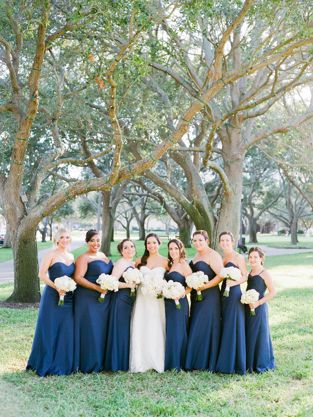 Outdoor Park Bridal Party Portrait, Bridesmaids in Floorlength Sweetheart Navy Blue Dresses with White Bouquets | Tampa Bay Wedding Hair Michele Renee The Studio | St. Petersburg Makeup LDM Beauty Group | Lindsay Does Makeup