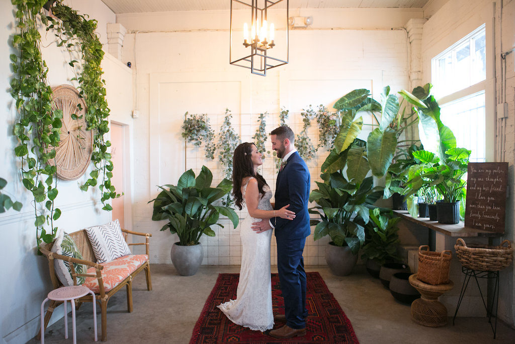 Indoor Bride and Groom Wedding Portrait, Bride Wearing V-Neck Lace Floor Length Wedding Dress, Curled Hair Down with Jeweled Hair Clip, Groom Wearing Navy Blue Suit | Tampa Bay Wedding Photographer Carrie Wildes Photography | Tampa Heights Wedding Venue Fancy Free Nursery