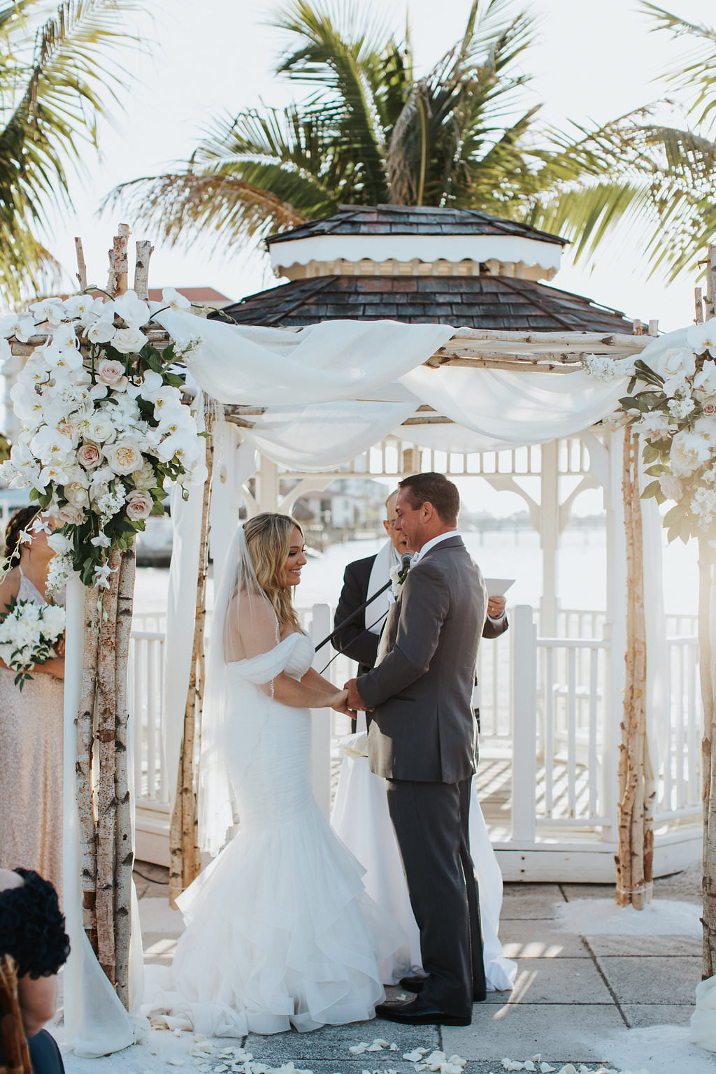 Outdoor Beach Wedding Ceremony Bride and Groom at Gazebo with Birchwood Arch, White Draping and White Florals   Waterfront Venue Isla Del Sol Yacht and Country Club