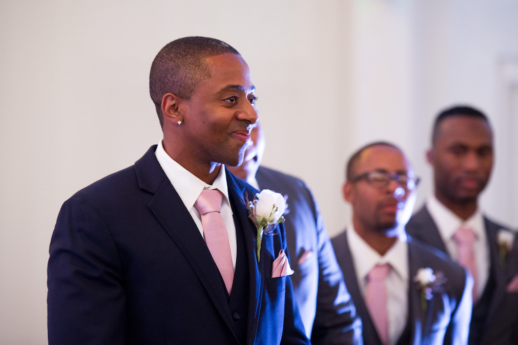 Groom's Reaction to Bride Walking Down the Aisle Wedding Ceremony Portrait in Navy Blue Suits, Blush Pink Ties, and White Rose Boutonniere