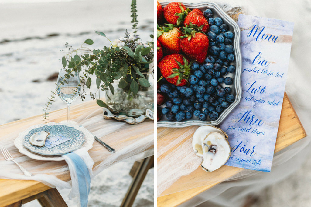 Waterfront Coastal Sandy White Redington Shores Wedding Reception Decor, Long Wooden Table with Decorative Blue Plate, Tulle and Blue Ribbon Linens, Greenery in Glass Vase | Blueberry and Strawberries on Silver Platter, Custom Coastal Watercolor Blue Menu and Oyster Shells