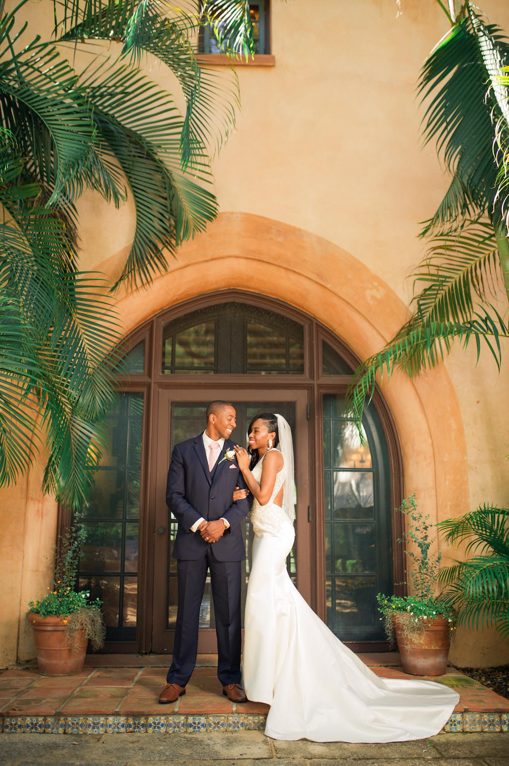 Outdoor Bride and Groom Portrait in V-neck Rhinestone Beaded Bodice and with Keyhole Back and Beaded Detailing Wedding Dress and Veil, Groom in Navy Blue Suit and Blush Pink Tie   Tampa Wedding Dress Shop Truly Forever Bridal