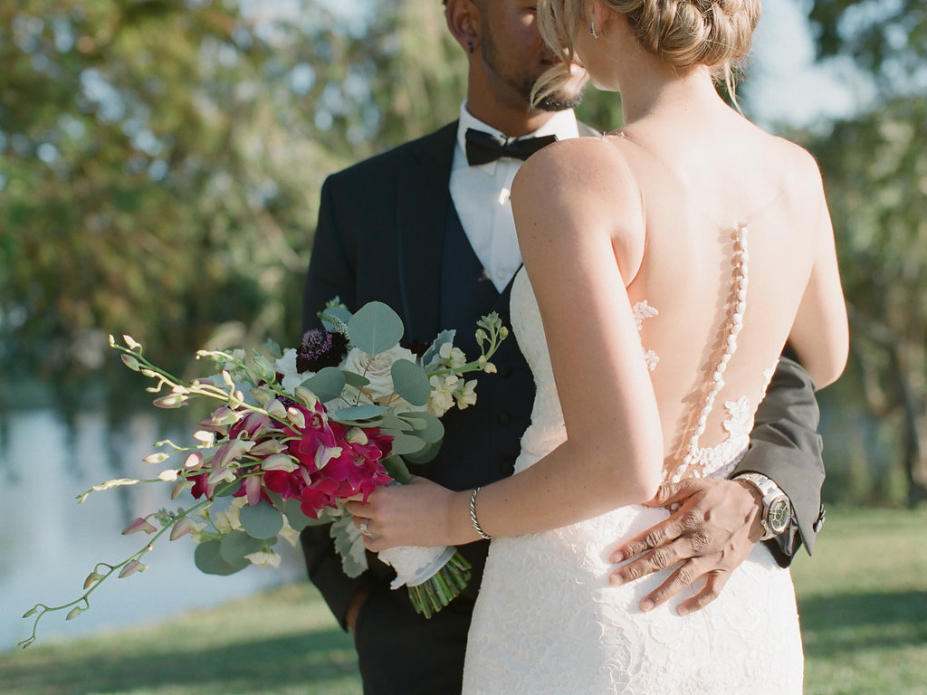 Intimate Outdoor Wedding Portrait, Bride in Spaghetti Strap Illusion Lowback Lace Dress with Buttons, Curled Hair Updo and Pink, Deep Purple, White and Greenery Floral Bouquet, Groom in Black Tuxedo and Black Bowtie
