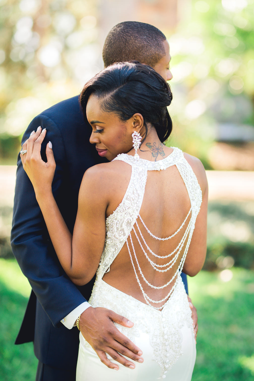 Outdoor Bride and Groom Portrait in V-neck Rhinestone Beaded Bodice and with Keyhole Back and Beaded Detailing Wedding Dress | Tampa Wedding Dress Shop Truly Forever Bridal