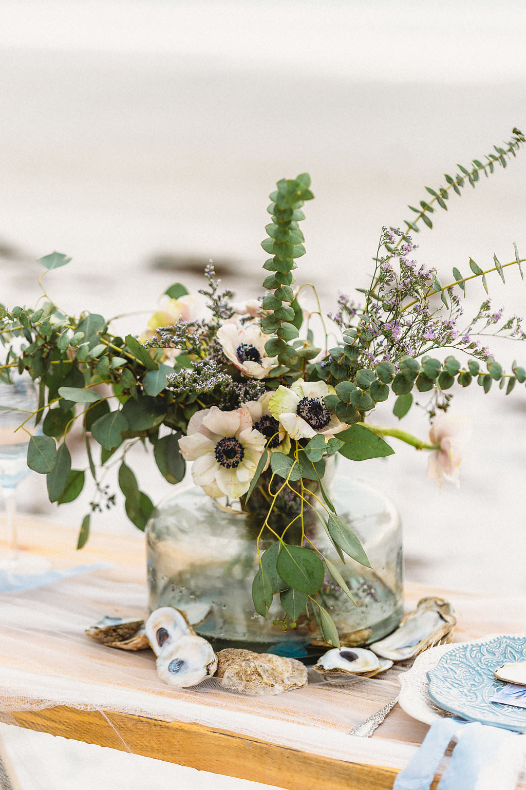 Waterfront, Coastal St. Pete Beach Wedding Reception Decor, Low Glass Vase with Greenery and White Anemone Floral Centerpiece with Oyster Shells
