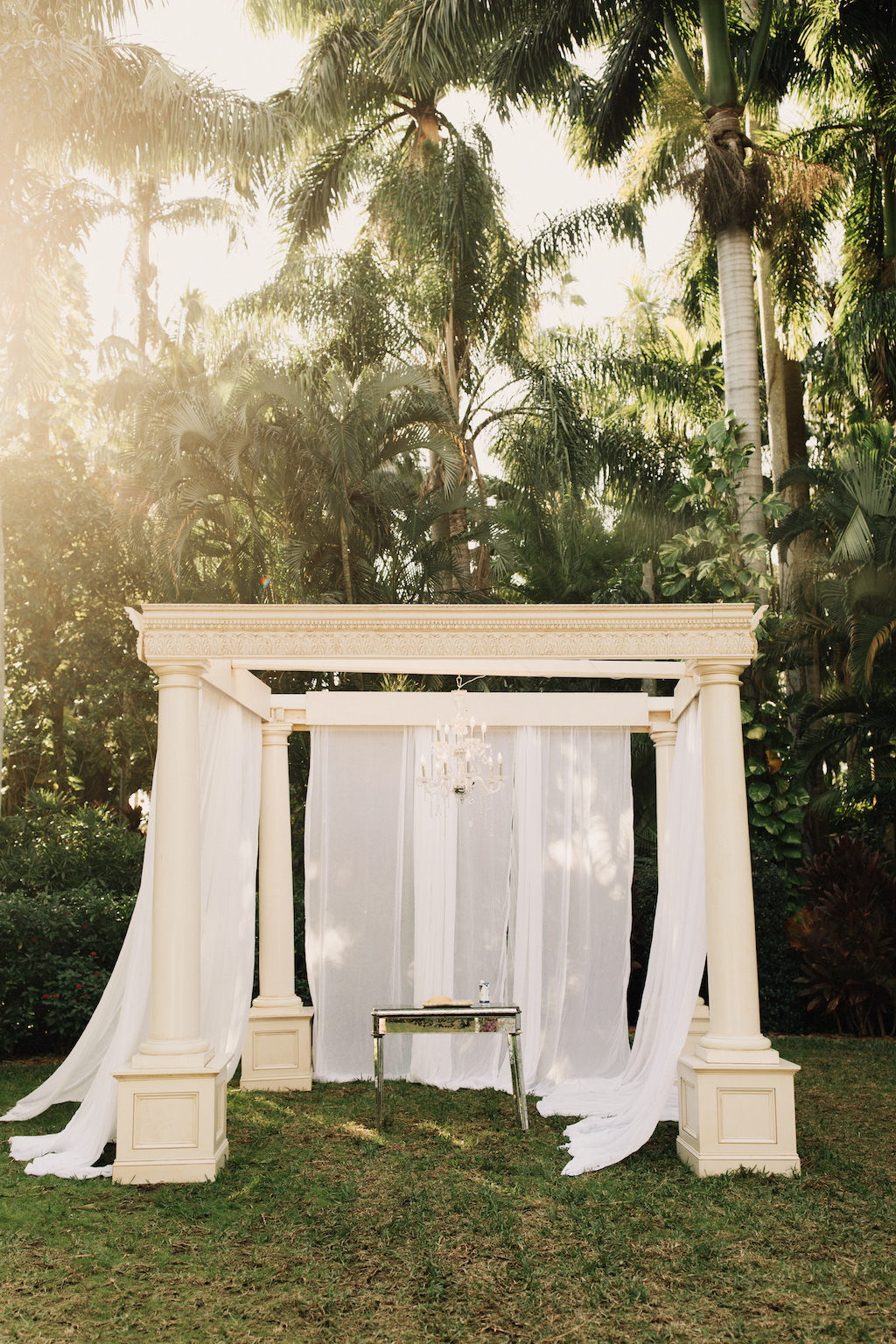 Elegant Outdoor Ivory Wedding Draped Ceremony Pillar Arch with White Drapery and Crystal Chandelier   St. Pete Wedding Venue The Sunken Gardens