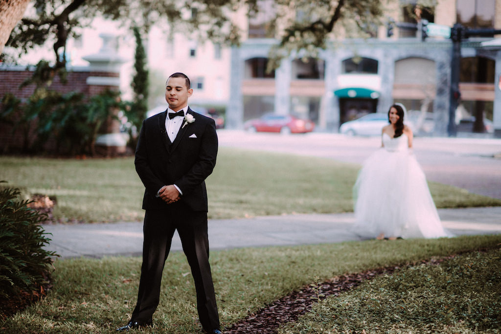 Outdoor Bride and Groom First Look Wedding Portrait, Groom in Black Tuxedo with Black Bowtie and White Rose Boutonniere, Bride in White Sweetheart Strapless Tulle Wedding Dress from The Bride Tampa