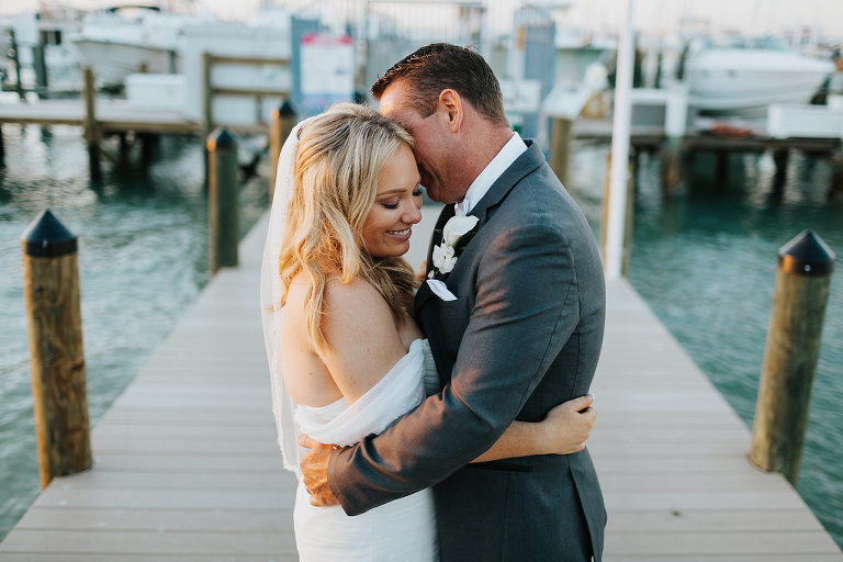 Romantic, Waterfront Bride and Groom Wedding Portrait, Bride in Mikaella Off the Shoulder, Sweetheart Wedding Dress and Tulle Veil, Groom in Grey Suit and White Cala Lillie Boutonniere | St. Pete Beach Wedding Venue Isla Del Sol Yacht and Country Club