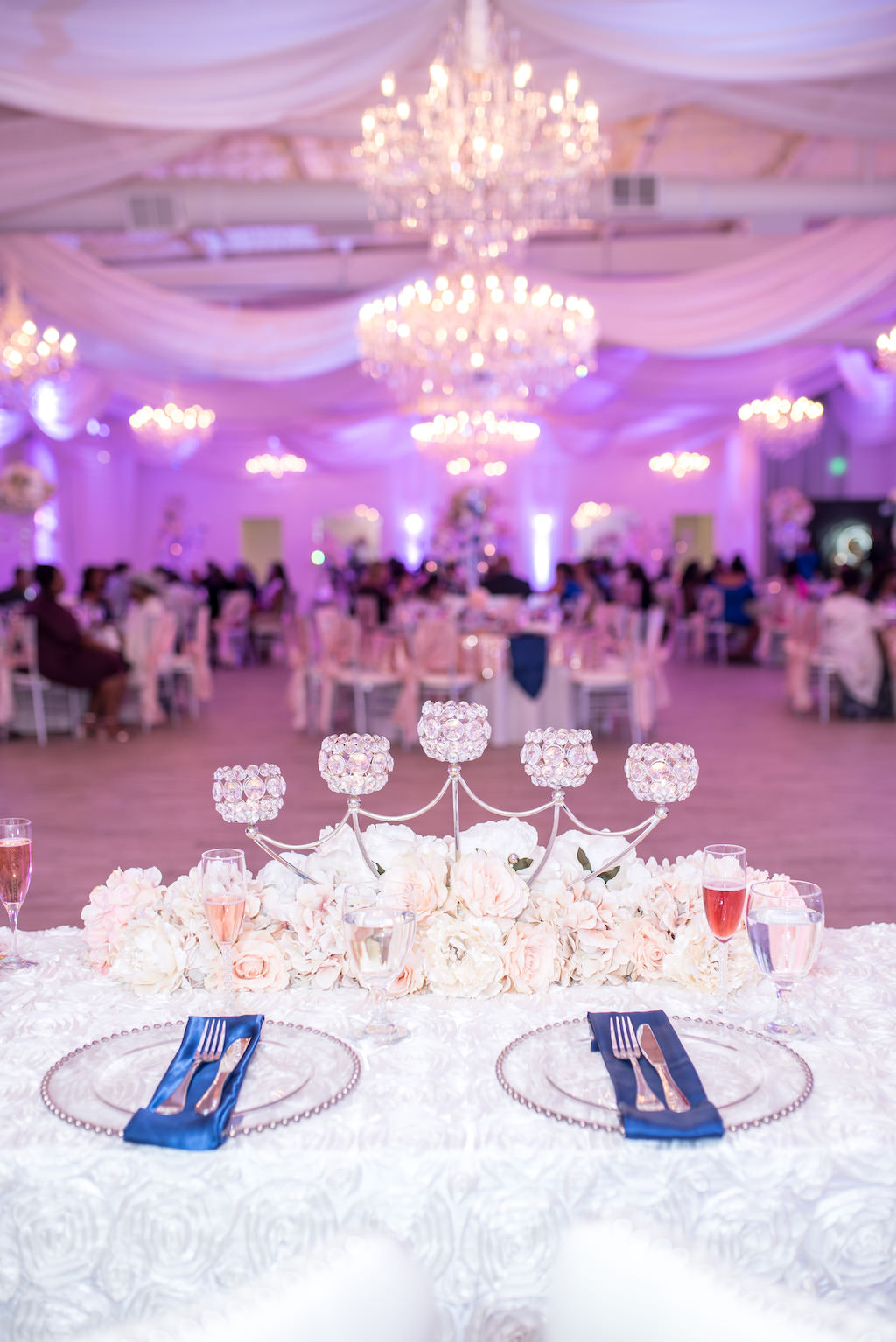 Indoor Wedding Reception Sweetheart Table Decor with White and Blush Pink Roses Centerpiece and Crystal Candle Holders, Clear Beaded Chargers, White Roses Tablecloth and White Draping and Chandeliers with Pink Uplighting   Tampa Bay Wedding Venue The Crystal Ballroom