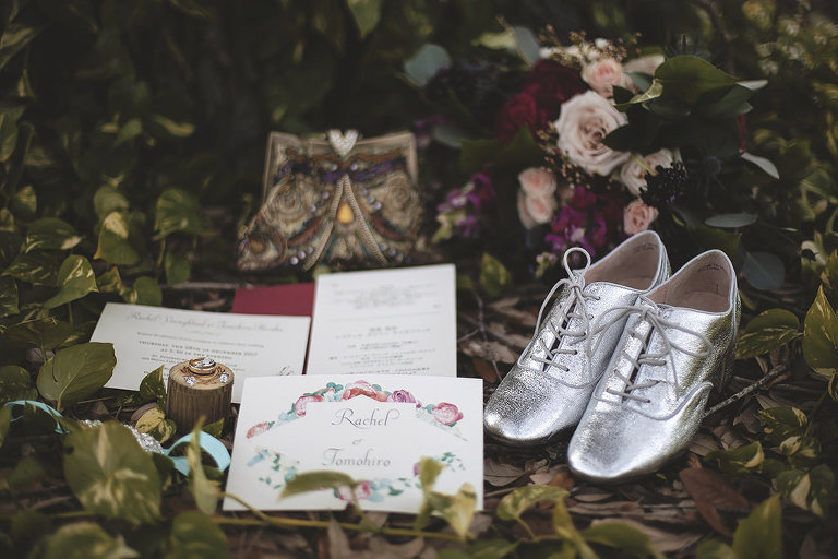 Old English Floral Inspired Wedding, White and Floral Invitation, Wedding Rings on Wooden Log, Men Silver Wingtip Shoes, Blush Pink, Dark Maroon and Greenery Bouquet on Leaves