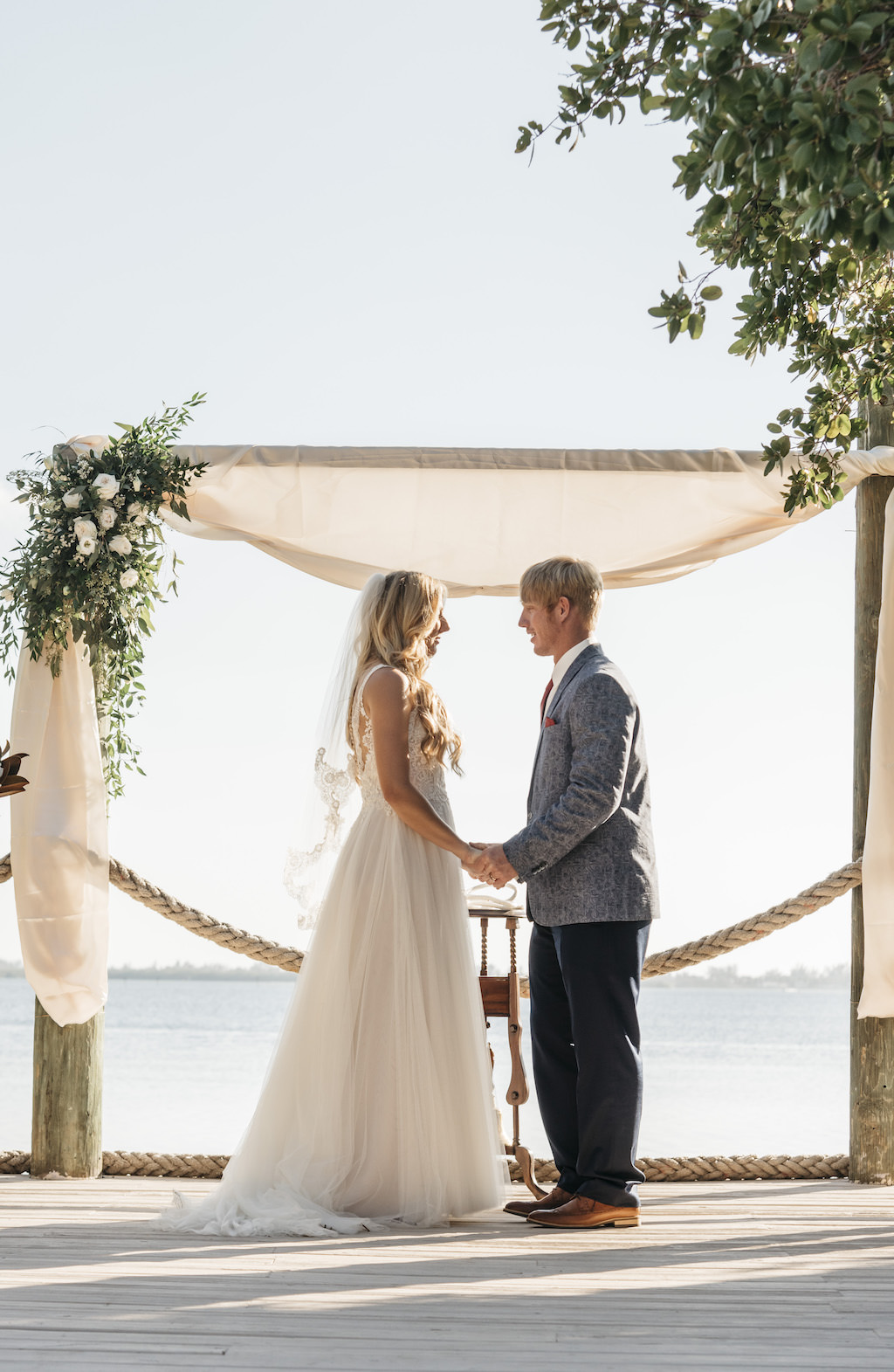 Outdoor Waterfront Bride and Groom Wedding Ceremony Portrait, Arch with White Draping and White and Greenery Bouquet | Tampa Bay Wedding Planner Kelly Kennedy Weddings and Events