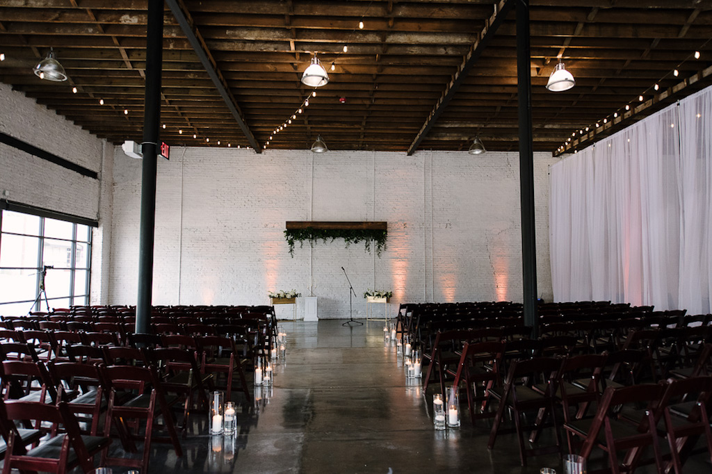 Modern, Industrial Wedding Ceremony Decor with Wooden Brown Folding Chairs and Floating Candles in Glass Vases | Lakeland Wedding Venue Haus 820 | Tampa Bay Rentals A Chair Affair