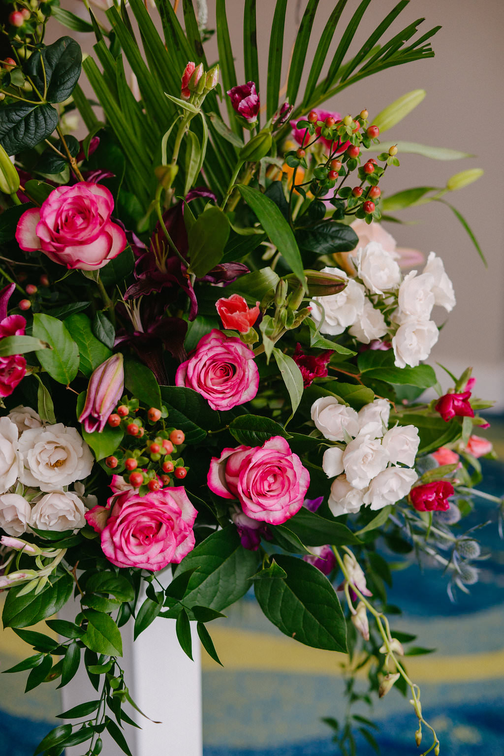 Tropical Inspired Wedding Ceremony Decor, Pink Roses, Berries, White and Greenery Bouquet on White Pedestal | Tampa Bay Wedding Photographer Grind and Press | Special Moments Event Planning