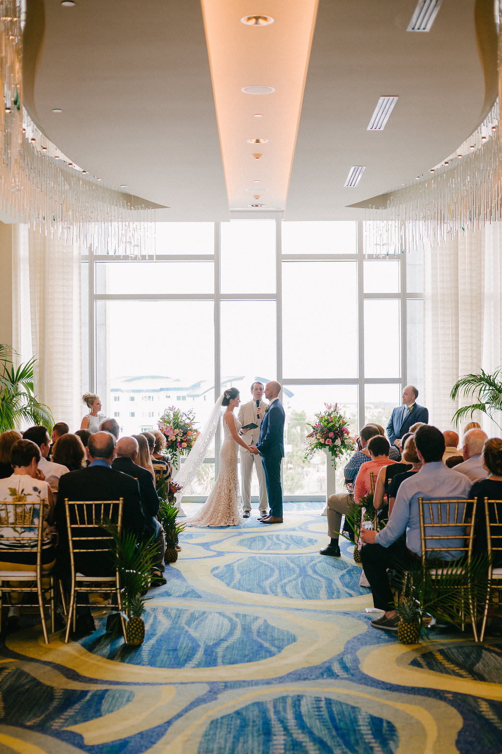 Indoor Hotel Wedding Ceremony Bride and Groom Portrait with Gold Chiavari Chairs and Tropical Florals | Tampa Bay Photographer Grind and Press | Clearwater Beach Opal Sands Resort | Special Moments Event Planning