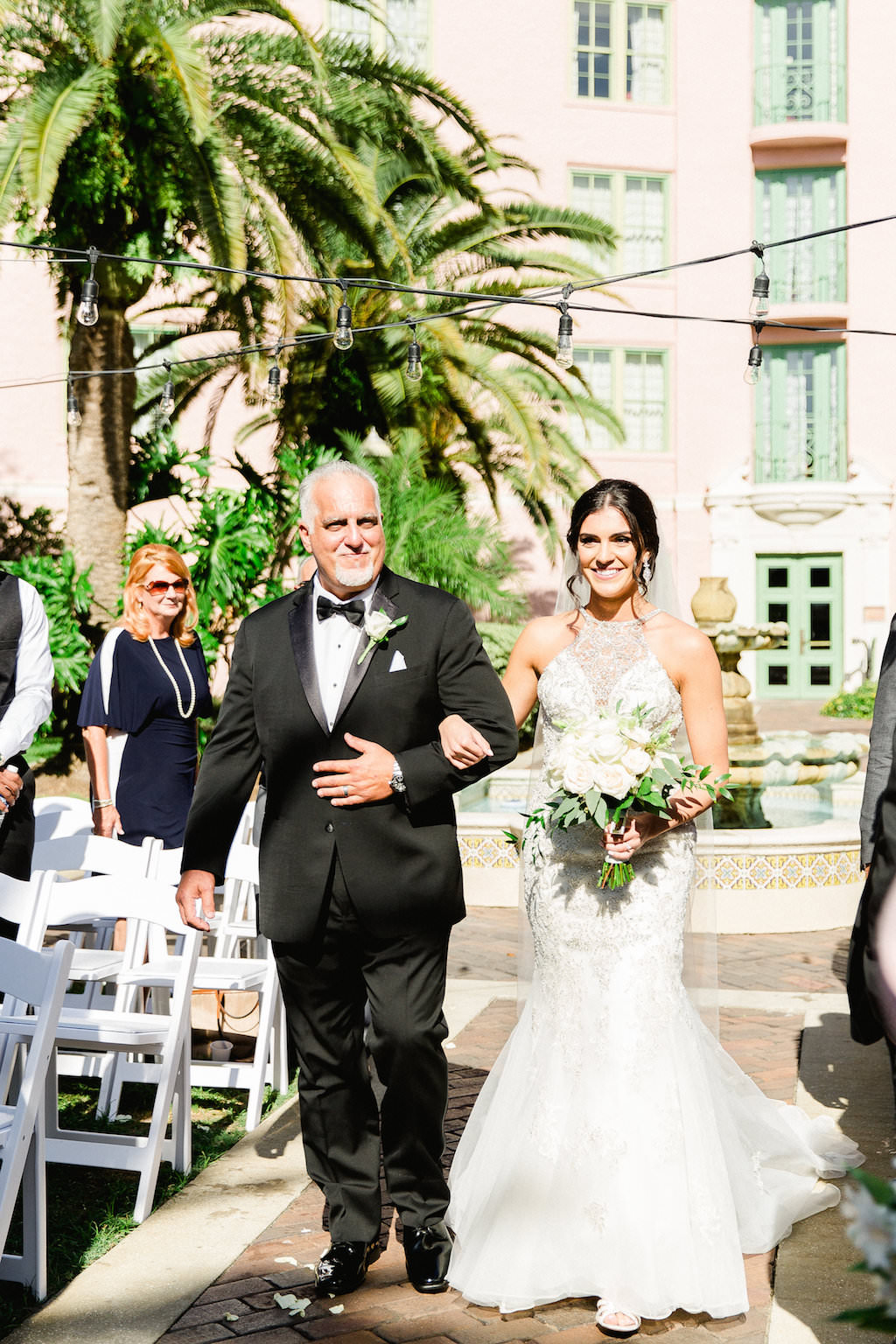 Bride Walking Down the Aisle with Father Ceremony Portrait, with White Rose and Greenery Bouquet, Bride in Fit and Flare Lace Halter Bodice Wedding Dress   Tampa Bay Wedding Photographer Ailyn La Torre   Venue The Vinoy Renaissance St. Petersburg Resort & Golf Club   Tampa Hair Artist Femme Akoi