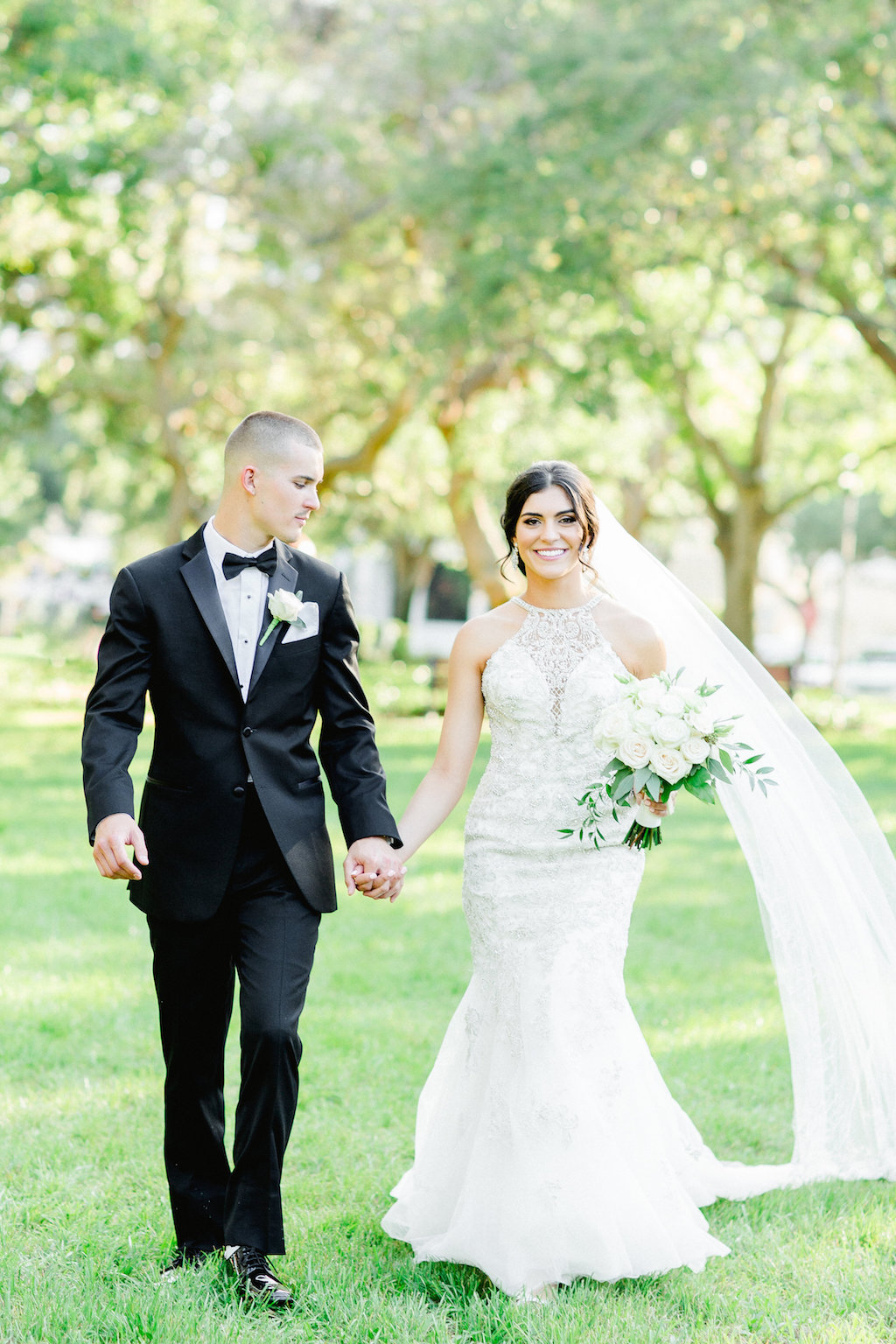 Outdoor Bride and Groom Wedding Portrait, Bride in Lace and Rhinestone High Neck Halter Fit and Flare Wedding Dress, Cathedral Length Veil, White and Greenery Bouquet, Groom in Black Tuxedo and White Rose Boutonniere   Tampa Wedding Photographer Ailyn La Torre   St. Petersburg Hair Artist Femme Akoi
