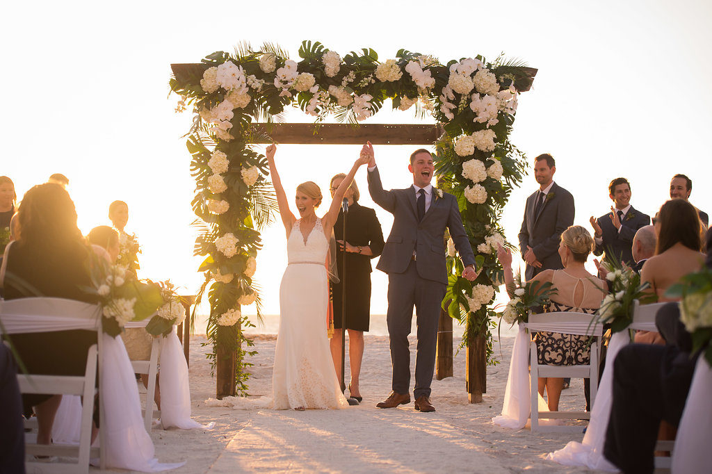 Clearwater Beach Wedding Ceremony Bride and Groom Portrait with White Folding Chairs Decorated with White and Greenery Floral Bouquets and Tulle, Wooden Arch with White Hydrangeas and Banana Leaf Florals | Tampa Wedding Planner Parties A La Carte | Tampa Bay Rental Company A Chair Affair | Clearwater Wedding Venue Carlouel Yacht Club