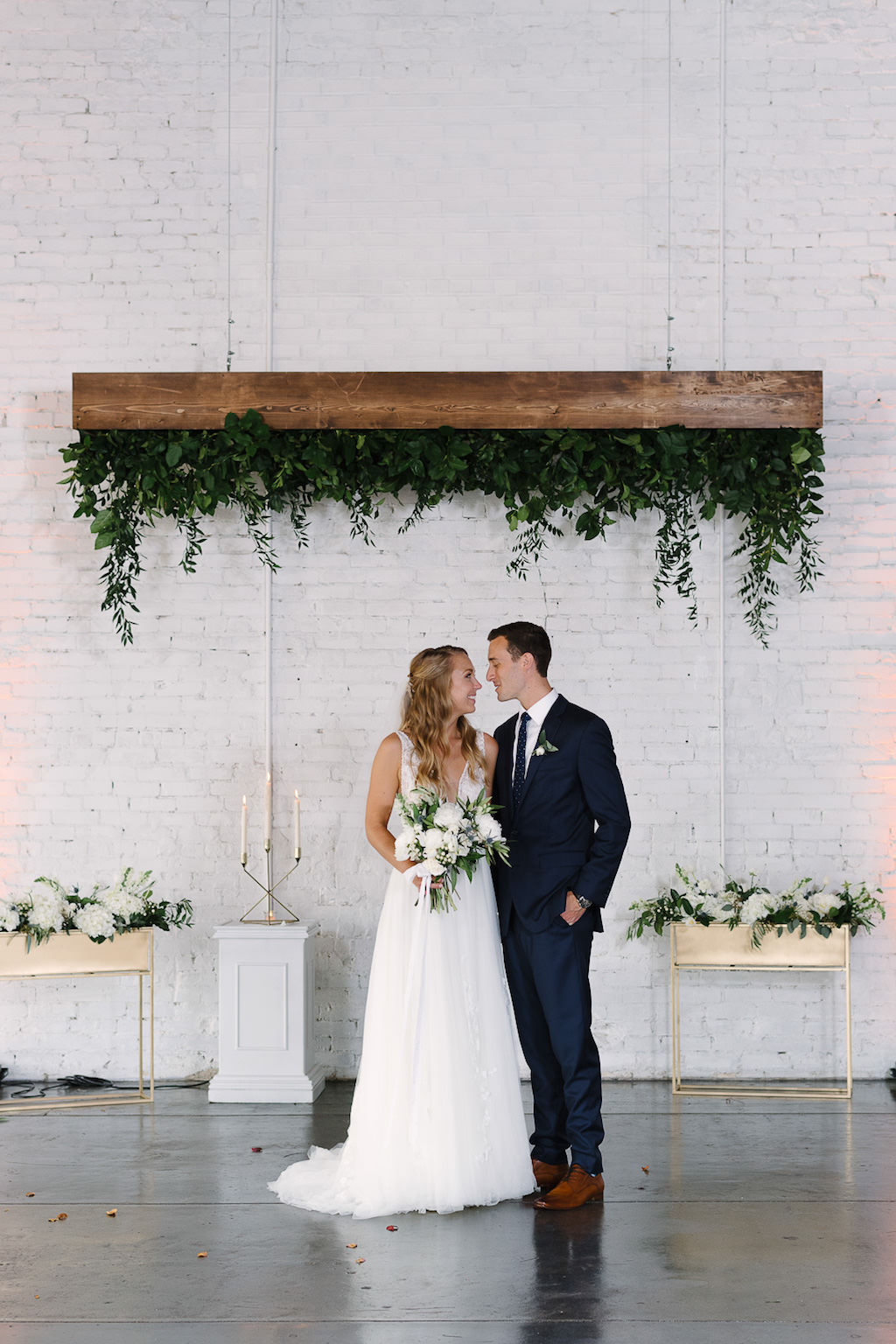 Romantic Bride and Groom Wedding Portrait, Groom in Navy Blue Suit and White Floral Boutonniere, Bride in White A-Line Illusion Tank Top Strap Plunging V-Neckline and Lace Bodice Wedding Dress with White Floral and Greenery Bouquet, Upside Down Wooden Planterbox and Green Plant, White Pedestal with Gold Candlestick, Gold Planter with White and Green Florals | Lakeland Wedding Venue Haus 820