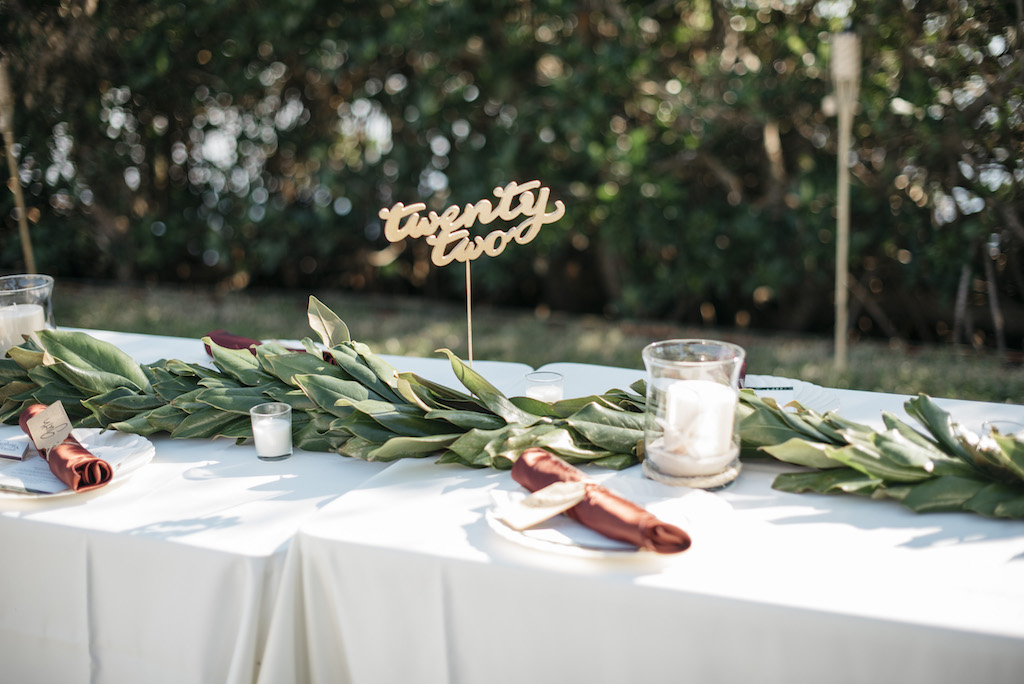 Outdoor Wedding Reception Decor Centerpieces Long Feasting Table with White Tablecloth, Long Greenery Garland, Burgundy Linens, Clear Class Hurricane Vase with Candle and Gold Lasercut Table Number | Tampa Bay Wedding Planner Kelly Kennedy Weddings and Events