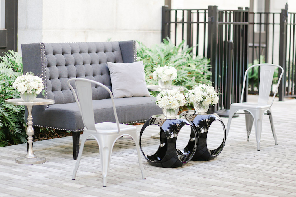 Elegant Outdoor Wedding Lounge Seating Area with High Back Modern Grey Couch, Black Cocktail Tables, Silver Chairs, Silver Side Table with Round Vase and White Rose and Greenery Flowers   Marry Me Tampa Bay and Isabel O'Neil Bridal Fashion Runway Show 2018   Tampa Wedding Photographer Lifelong Photography Studios   Planner Love Lee Lane   Tampa Bay Rentals Kate Ryan Event and A Chair Affair   Historic Downtown Tampa Wedding Venue Le Meridien