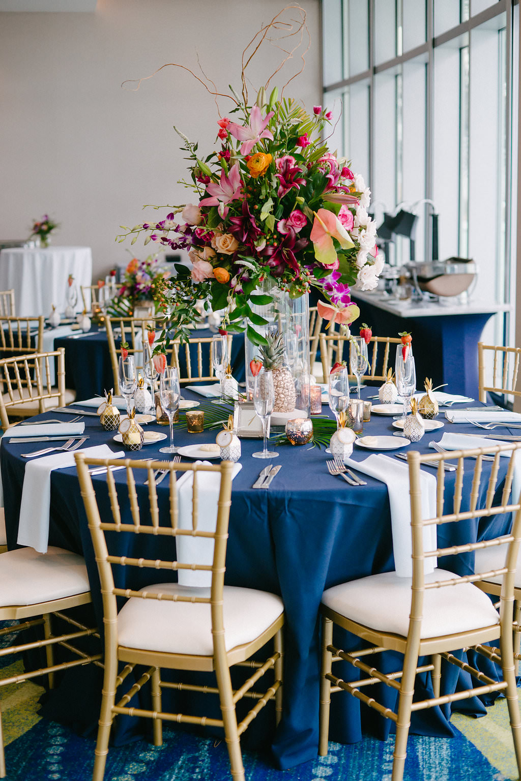 Hotel Ballroom Wedding Reception Decor, Round Tables with Navy Blue Tablecloth, White Linen, Tropical Inspired Floral Centerpiece, Pink, Purple, Burnt Orange, and Greenery Flowers in Glass Vase, Gold Chiavari Chairs and Gold Pineapple | Tampa Bay Photographer Grind and Press Photography | Planner Special Moments Event Planning | Clearwater Beach Venue Opal Sands Resort