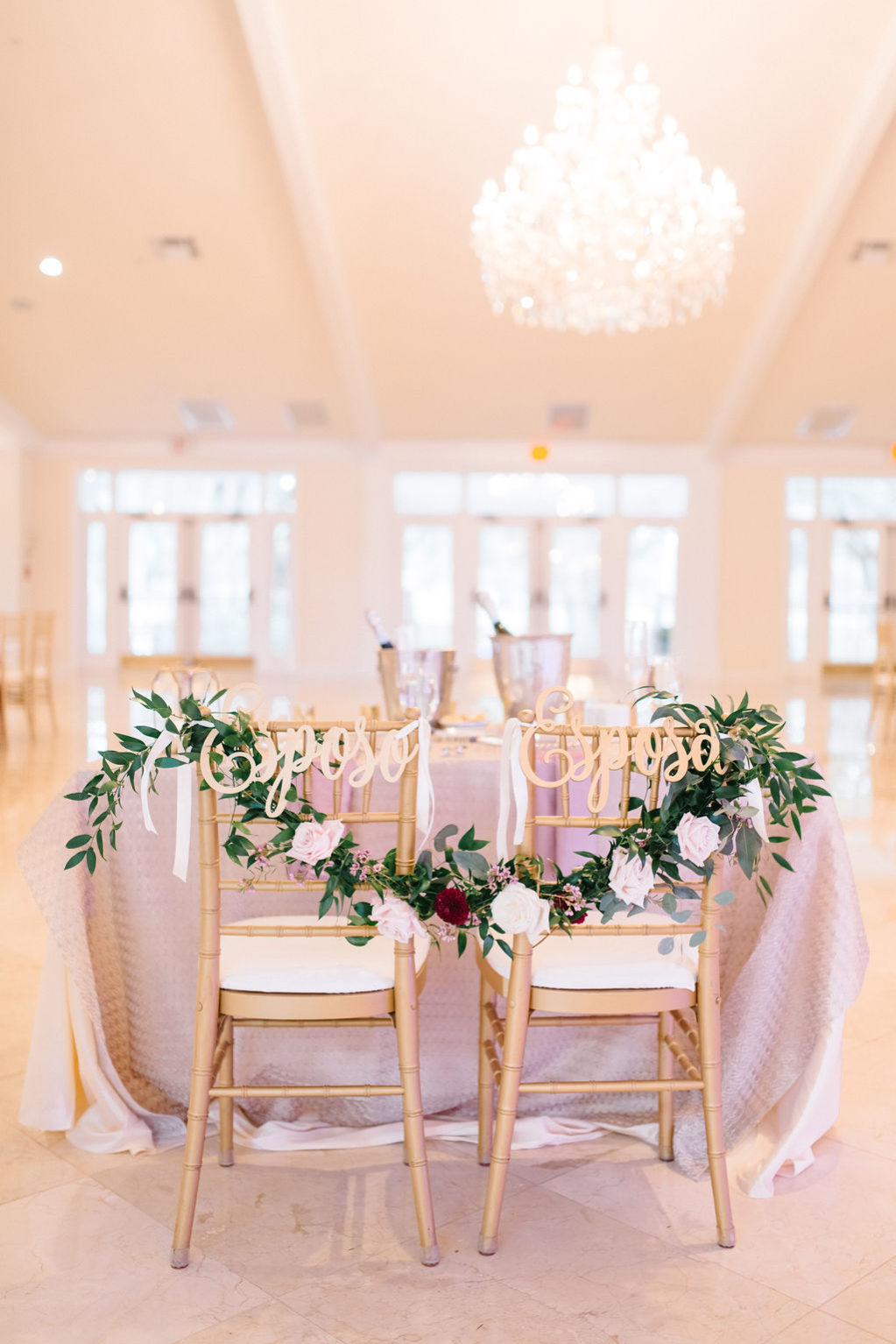 Elegant Wedding Reception Decor Sweetheart Table with Lilac Tablecloth, Gold Chiavari Chairs, Green Garland with White and Blush Roses and Laser Cut Gold Groom and Bride Chair Signs | Tampa Bay Wedding Planner Burlap to Lace
