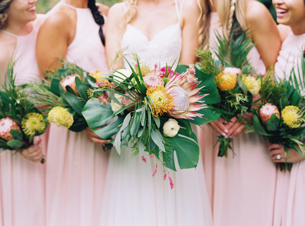 Outdoor Bride and Bridesmaid Portrait in Long Blush Pink Matching Dresses, Bride in Strappy V-neck Lace Wedding Dress with Tropical Pink, Yellow and Greenery Bouquets | St. Pete Wedding Planner Southern Glam Events and Weddings
