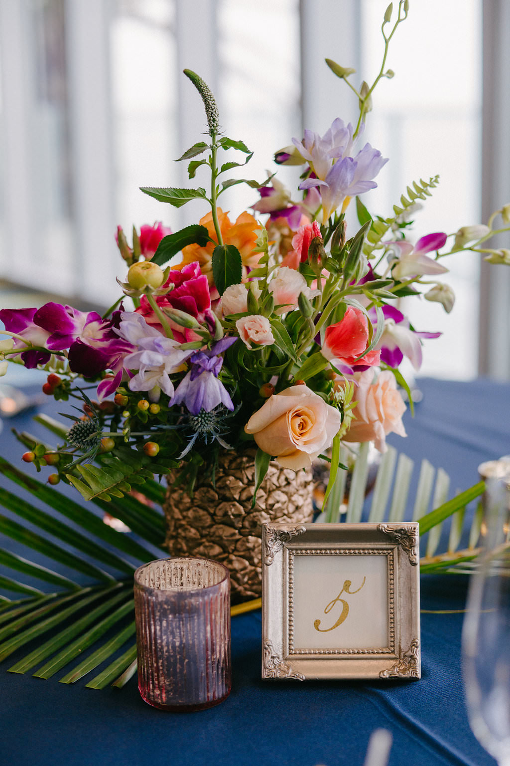 Hotel Ballroom Wedding Reception Decor, Tropical Floral Bouquet in Gold Pineapple, Pink, Purple, Peach, White and Greenery Flowers, Table Number in Gold Frame, Candle Votive, Palm Leaf Branch on Navy Blue Linen | Tampa Bay Photographer Grind and Press | Special Moments Event Planning