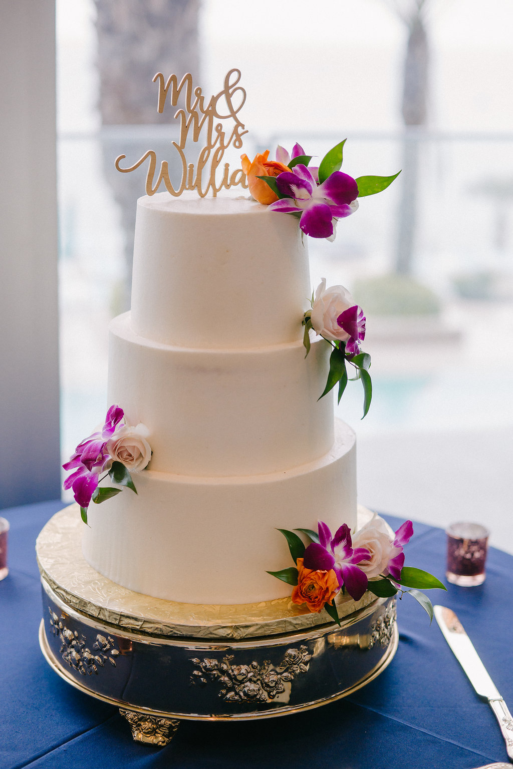 Three Tier White Buttercream Wedding Cake with Real Purple Orchids and Orange Rose Accents, Lasercut Personalized Cake Topper on Gold Cake Stand | Tampa Bay Photographer Grind and Press | Clearwater Beach A Piece of Cake