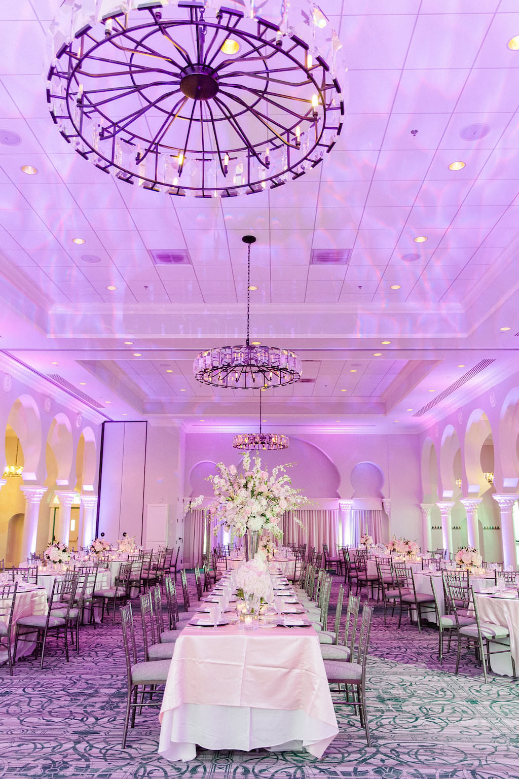 Elegant Ballroom Reception Decor, Long Banquet Table with White Linen and High White Floral Centerpiece, Purple/Pink Uplighting, Silver Chiavari Chairs | Tampa Wedding Photographer Ailyn La Torre | Venue The Vinoy Renaissance St. Petersburg Resort & Golf Club