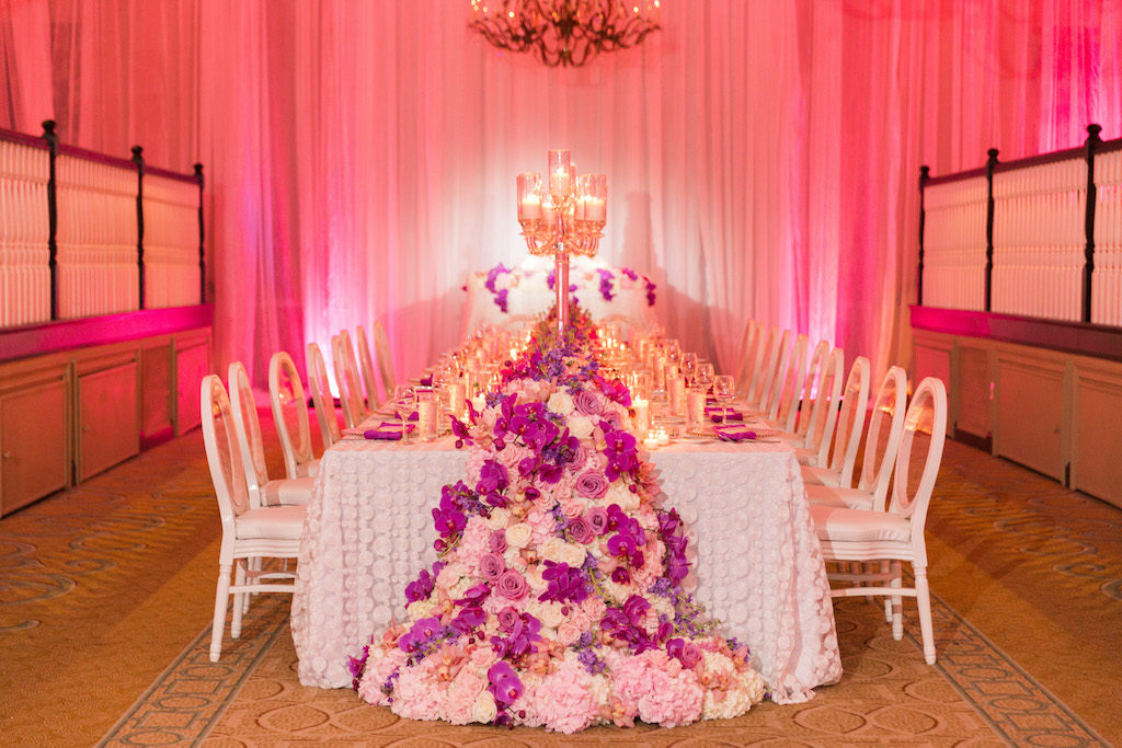 Elegant Ballroom Reception Decor, Long Feasting Table with Decorative White Linen, Fuchsia, Pink and White Floral Garland, Tall Candlestick and White Chairs and Pink Uplighting and Linen Draping | St. Pete Beach Historic Wedding Venue The Don Cesar | Florist Bruce Wayne Florals