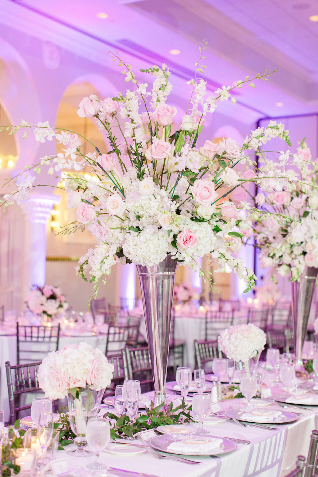 Elegant Ballroom Reception Decor, Long Banquet Table, White Linen, High and Low White and Blush Pink Floral Centerpieces in Silver Vase, Purple/Pink Uplighting, Silver Chiavari Chairs   Tampa Wedding Photographer Ailyn La Torre   Venue The Vinoy Renaissance St. Petersburg Resort & Golf Club