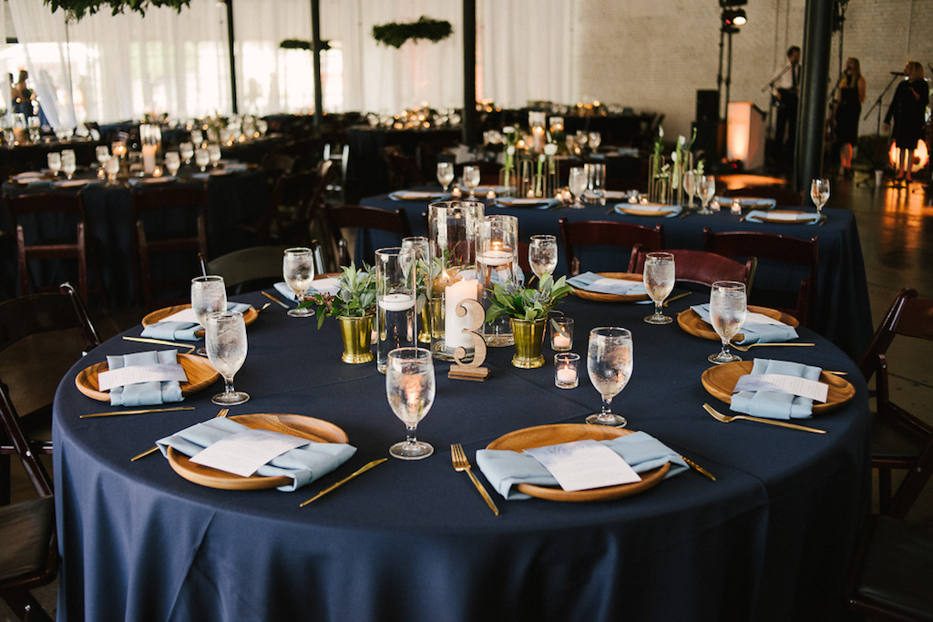 Navy Blue Wedding Reception Round Table Decor with Blue Satin Linen, Wooden Chargers with Dusty Blue Linen, Lasercut Table Number, Floating Candles in Glass Vases, Green Plant in Gold Vase | Lakeland Venue Haus 820 | Tampa Bay Rentals Over the Top Linens