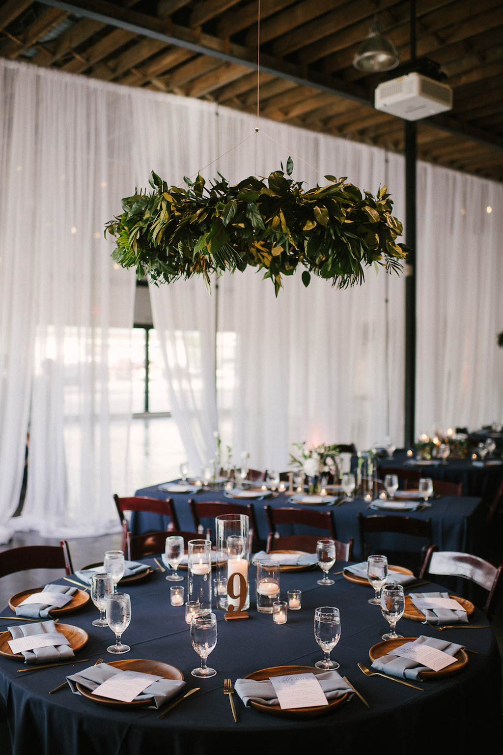 Navy Blue Wedding Reception Round Table Decor with Blue Satin Linen, Wooden Chargers, Lasercut Table Number, Floating Candles in Glass Vases, and Green Hanging Plant | Lakeland Venue Haus 820 | Tampa Bay Rentals Over the Top Linens