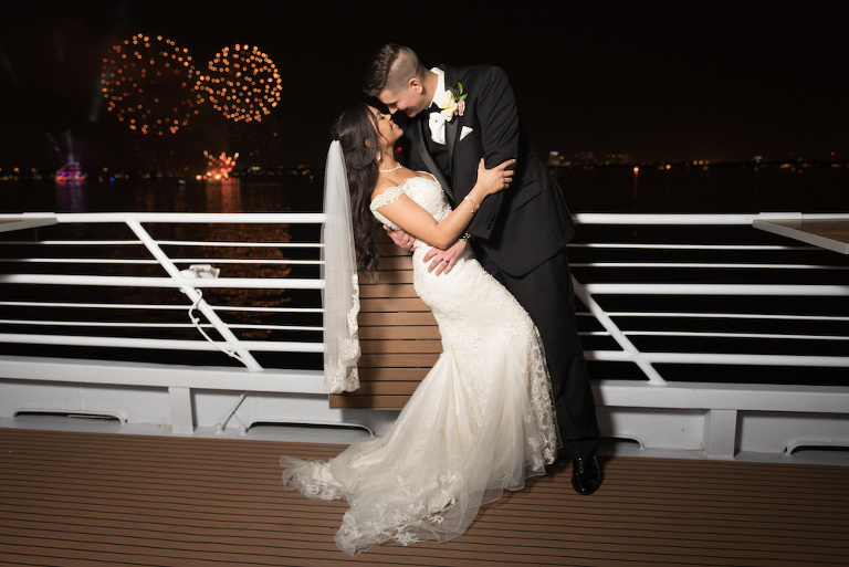 Outdoor Waterfront Nighttime and Fireworks Wedding Bride and Groom Portrait, Bride with Lace Off the Shoulder Wedding Dress and Veil, Groom in Black Tuxedo and Rose Boutonniere | Tampa Bay Nautical Wedding Venue Yacht StarShip