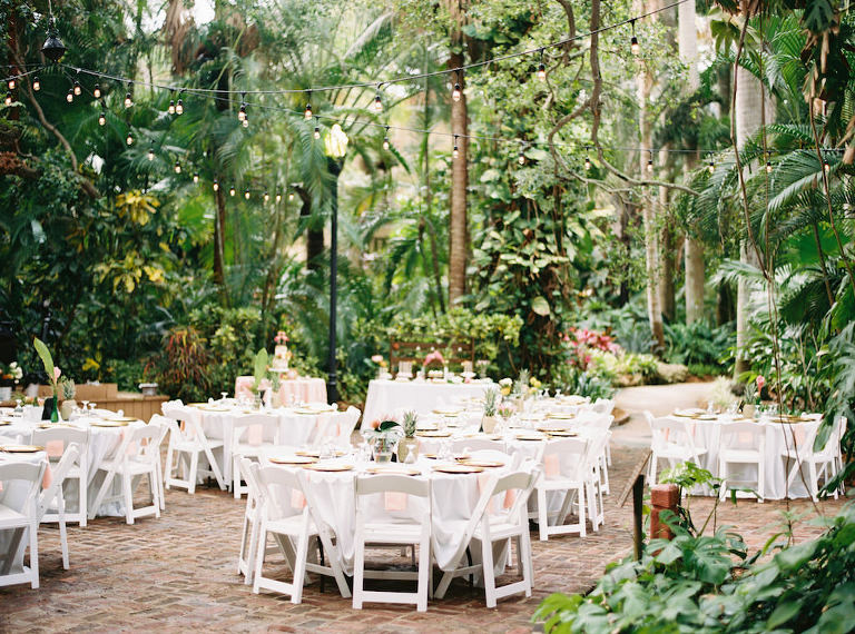Outdoor Tropical Garden Wedding Reception Decor, Round Tables with White Tablecloth, White Folding Chairs and Gold Pineapple Centerpiece | Outdoor St. Petersburg Wedding Venue Sunken Gardens | Planner Southern Glam Events and Weddings