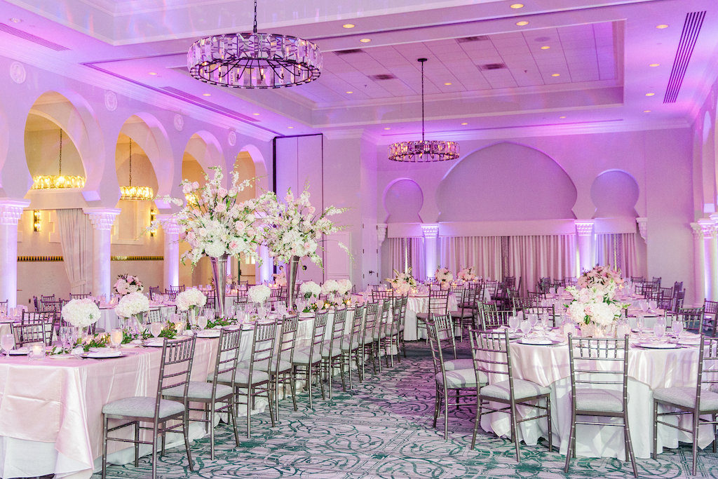 Elegant Ballroom Reception Decor, Long Banquet Table and round Tables with White Linen, High and Low White Floral Centerpieces, Purple/Pink Uplighting, Silver Chiavari Chairs | Tampa Wedding Photographer Ailyn La Torre | Venue The Vinoy Renaissance St. Petersburg Resort & Golf Club