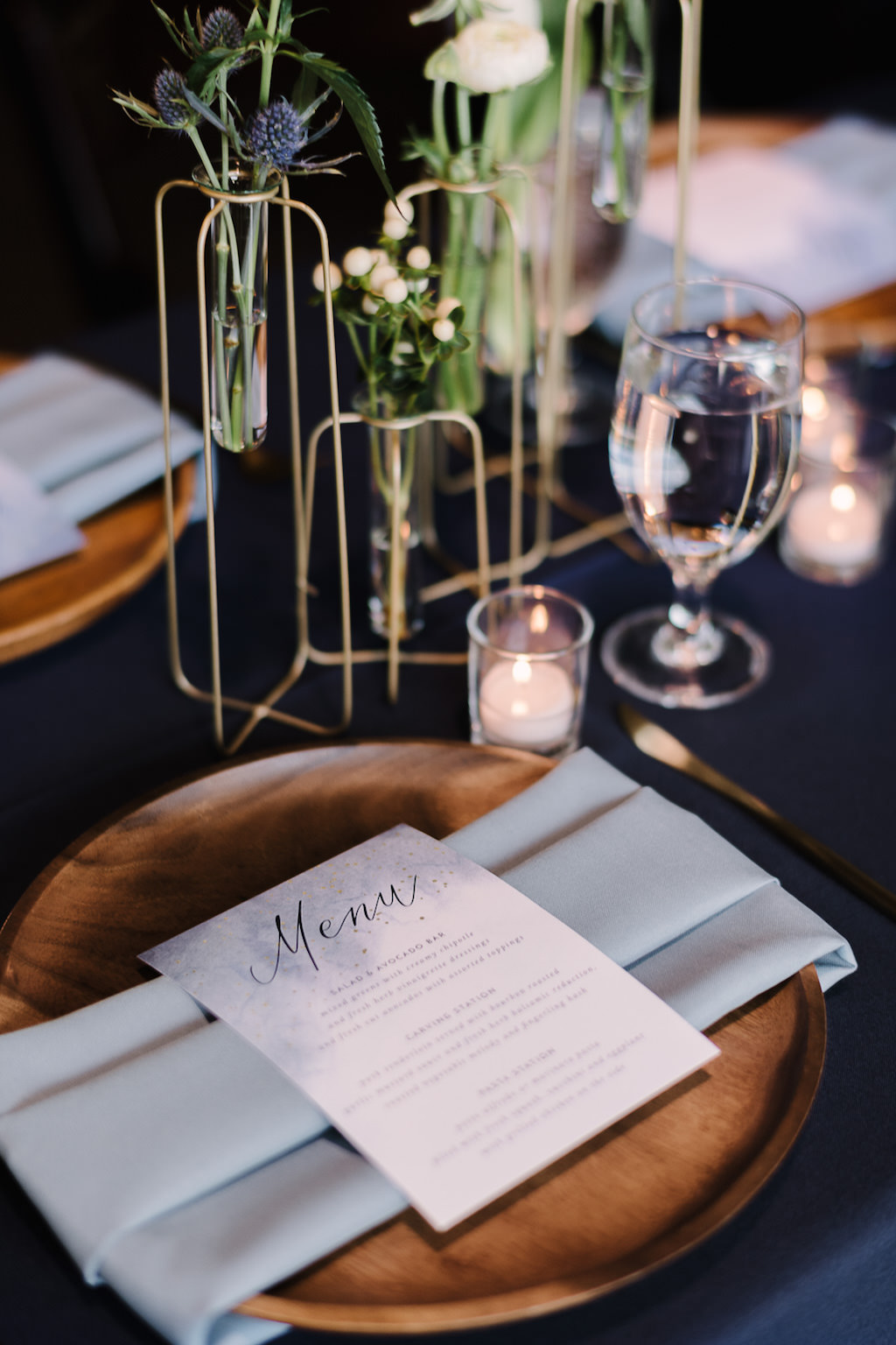 Wooden Charger with Dusty Blue Linen and Menu, Gold Wire Vases with Green Florals | Tampa Bay Rentals Over the Top Linens